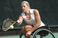 Vergeer playing a right hand forehand tennis stroke while seated in her wheelchair