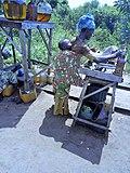 Femme avec son enfant au dos se prépare pour servir de l'essence frelatée au client a porto novo-Bénin.jpg