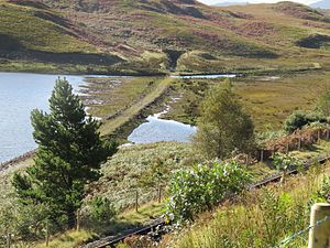 Ffestiniog Power Station - The old route of the Ffestiniog Railway, showing the northern portal of Moelwyn Tunnel, often submerged below the waters of Tanygrisiau reservoir, but visible here because of low water levels. The replacement FR route is in the foreground.