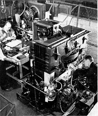Betatron - Early betatron at University of Illinois. Kerst is at right, examining the vacuum chamber between the poles of the 4-ton magnet.