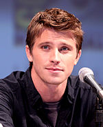 Garrett Hedlund in front of a microphone during a press conference.