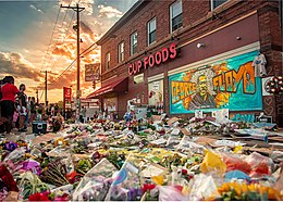 Large area of sidewalk covered in flowers and other tributes beside a building with a mural painted on the wall