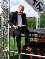 Galloway signing an asylum seekers petition, sitting on the edge of the StWC stage at the 2005 Make Poverty History rally.