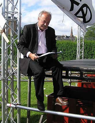 George Galloway - Galloway signing an asylum seekers petition, sitting on the edge of the StWC stage at the 2005 Make Poverty History rally.