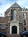 Ingangspoort van koor van Sint Janskerk met natuursteen versierd, door Haarlems wapen in cartouche bekroond