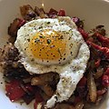 Hashed brown potatoes with red bell peppers and bacon, topped with a fried egg. -breakfast.jpg
