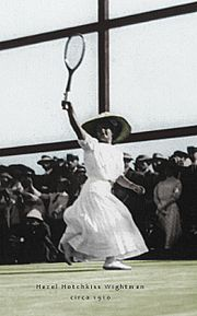 A women in all white attire is hitting a backhand with the tennis racket in the right hand, which it is a black and white photograph