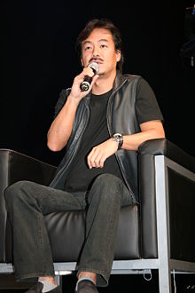 Hironobu Sakaguchi holding a microphone, seated on a black leather chair, with black jeans, a black shirt, and a black leather vest