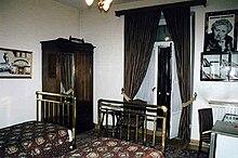 Photographie en couleur d'une chambre d'hôtel avec des souvenirs de Christie sur les murs