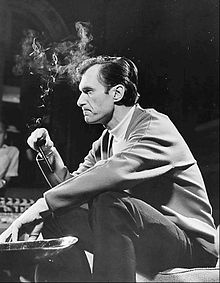 Black-and-white photo of a seated Hugh Hefner, smoking his trademark pipe