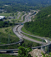 A view of a freeway leaving an interchange from a mountaintop, heading between development to the left and mountains to the right