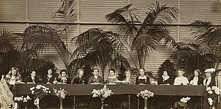 A black and white photograph of thirteen women delegates seated at a head table of a conference
