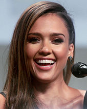 A portrait shot of Jessica Alba, an attractive women with long brown hair, smiling