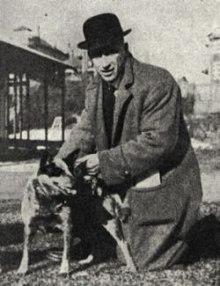Ein Mann von etwa 30 Jahren mit dunklem Mantel und einem schwarzen Hut, einer Melone, auf dem Kopf. Er kniet auf dem Boden und streichelt einen mittelgroßen Hund