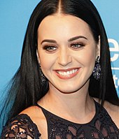 A woman with pale skin, green eyes and a long dark hair and wearing a dark dress smiles to the camera.