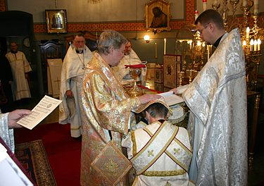 Eastern Orthodox subdeacon being ordained to the diaconate. The bishop has placed his omophorion and right hand on the head of the candidate and is reading the Prayer of Cheirotonia. Kheirotonia.jpg