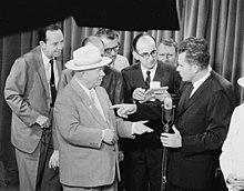 Nixon tient un micro et discute avec un homme portant un chapeau. Plusieurs personnes en costume se tiennent autour des deux hommes.