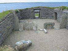 A small area of gravel is enclosed by a stone wall built into the surrounding grassy fields. Various large stones sit inside this enclosure and a low doorway has been constructed at the far end. Beyond the doorway, there is a rocky foreshore and a body of water.