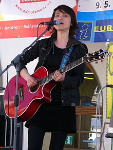 Young, dark-haired woman in black playing red acoustic guitar on stage