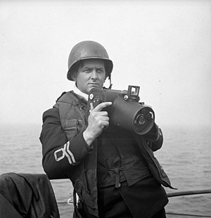 Royal Canadian Naval Volunteer Reserve - Lieutenant Gilbert A. Milne of the Royal Canadian Naval Volunteer Reserve, holding a Fairchild K20 camera
