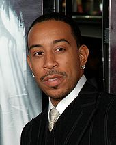 A man wearing a striped suit and earrings.
