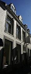 foto van Huis met lijstgevel, voorzien van omblokte vensters, waarvan de kruisen zijn uitgebroken.