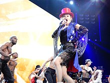 "Madonna flanked by her dancers performing ""Holiday"". All of them wear black cloths."