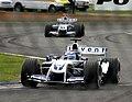 Marc Gene - Williams FW26 heads team mate Juan Pablo Montoya during practice for the 2004 British Grand Prix (50830957068).jpg