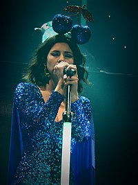 A light-skinned brown-haired woman is wearing a long-sleeved sparkling blue dress and a headpiece shaped like a pair of sparkling blue cherries, and is seen singing into a microphone.