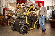 Matteo Maestri, CEO of Estrima, standing beside a Birò microcar in what seems to be an apartment