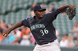 "A man in a blue baseball uniform with the word ""Mariners"" partially obstructed and a blue cap with the letter ""S"" prepares to throw a pitch with his right arm."