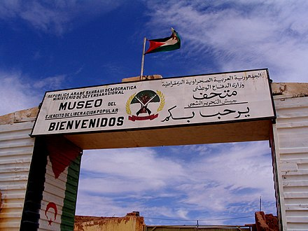 Bilingual signage of Museum of the Sahrawi People's Liberation Army in Western Sahara written in Spanish and Arabic. Museo de la Guerra en Rabuni, sede del gobierno de la RASD.jpg