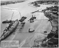 NASPH ^118523- 3-28-43, USS Oklahoma- Salvage, Aerial view looking forward on inshore side with ship in 40 degree... - NARA - 296978.tif
