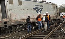 Four investigators look at one of the damaged train cars with Amtrak marked on the side