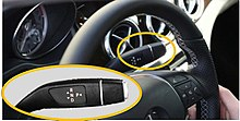 A rectangular image showing the upper part of a black automobile steering wheel, with a hand at lower right and a dashboard visible in the background. A yellow ellipse is around a small lever protruding from the right of the steering column behind the wheel; in the lower left quarter of the image is a closer view of this lever, also within a yellow ellipse. On the lever the letters R, N and D in white are arranged top to bottom in a central column with triangles pointing in opposite directions next to them on the left, and a letter P with a triangle pointing away from it on the right.