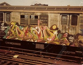 A subway car covered with graffiti can be seen. The image has faint amounts of yellow throughout.