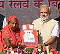 Narendra Modi handing over the certificates etc. to select beneficiaries of various welfare schemes of the Union and State Governments.JPG