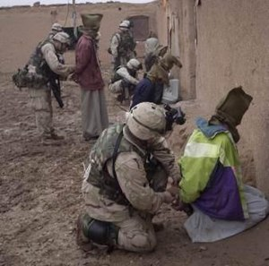 Hood event - Soldiers from the 173rd Airborne Brigade placing hoods over the heads of suspected Iraqi insurgents in December 2003.