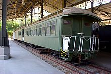 A set of old, green-colored passenger cars