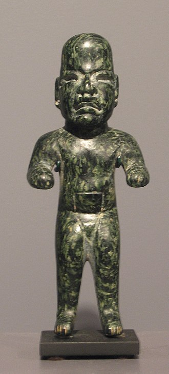 """Olmec figurine - An """"elongated man"""" figurine, dark green serpentine. Inlays, since lost, once animated the eyes, ears, nose, and mouth."""