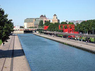 Canal de l'Ourcq - The Canal de l'Ourcq as seen from the Parc de la Villette. In the  background are the Grands Moulins de Pantin