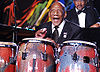 A man wearing a tuxedo is playing the congas