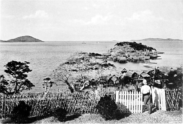 Black and white photograph of the view from a hilltop. The sea and islands are visible in the distance, with a man and a fence in the foreground.