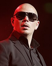 A bald man is wearing dark glasses and black tuxedo
