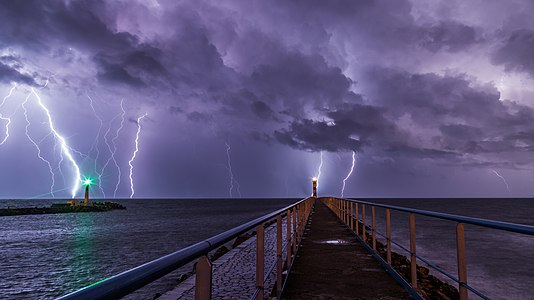 Port and lighthouse overnight storm with lightning in Port-la-Nouvelle