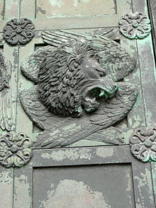 A relief with lion's head facing right with bared teeth over four folded wings and a frame with floral bosses at each corner