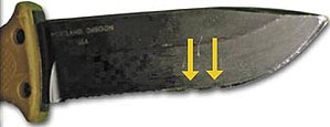 Aircrew Survival Egress Knife - A Gerber LMF II ASEK used to sever a 220 volt line; arrows point to the minor damage done to the cutting edge by the current.