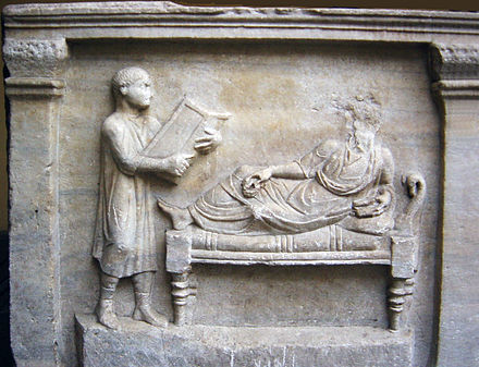 Slave holding writing tablets for his master (relief from a 4th-century sarcophagus) Sarcofago avvocato Valerius Petrnianus-optimized.jpg