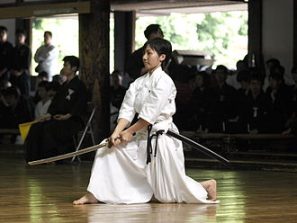 Iaitō - Japanese girl practicing iaido. The iaitō shown in this photograph was custom made according to the weight and size of the student. The blade is made of aluminum alloy, and for the student's safety, lacks a sharp edge