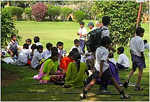 a group of school students moving and or sitting in a park